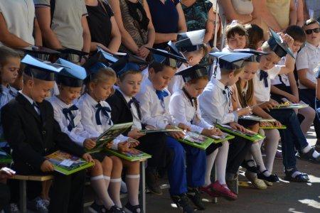 Mali uczniowie w odświętnych strojach siedzą w pierwszym rzędzie. Na kolanach kolorowe książki i kredki. W drugim rzędzie stoją dorośli.