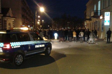 Grupa uczestników Drogi Krzyżowej wchodzi na pl. Kościuszki. Z tyłu widać samochód Straży Miejskiej