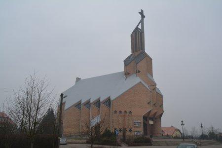 Kościół św. Piotra Apostoła. Geometryczna bryła budowli zbudowane z cegły ma liczne pionowe uchyłki ścian, trójkątne wykończenia dachu. Wieża umiejscowiona nad głównym wejściem zwieńczona krzyżem
