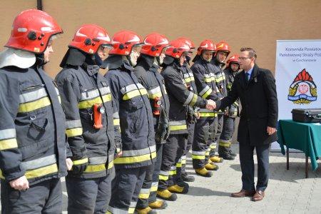 Po lewej rząd strażaków pełnym umundurowaniu. Prezydent Ciechanowa podaje rękę kolejnemu ze strażaków