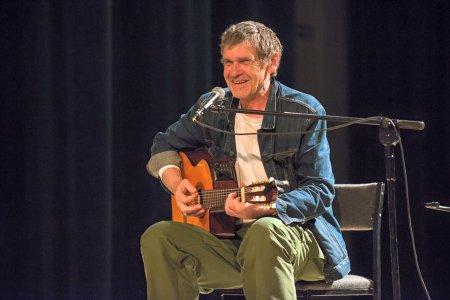 Uśmiechnięty Lech Dyblik siedzi na krześle. Gra na gitarze, przed nim stoi mikrofon