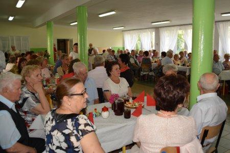 Spotkanie z seniorami. Seniorzy siedzą przy długich stołach ustawionych w kształt litery U