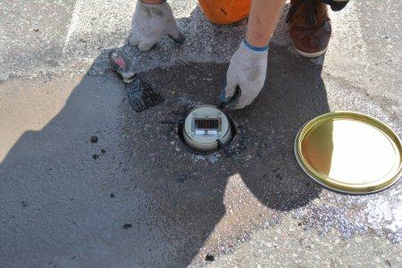 Pracownik montuje w asfalcie okrągłą lampkę, która będzie świecić po zmierzchu