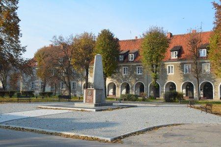 Plac Piłsudskiego. Na pierwszym planie kolumna upamiętniająca Marszałka, w tle krzywa hala. Między pomnikiem i krzywą halą w jesiennych barwach
