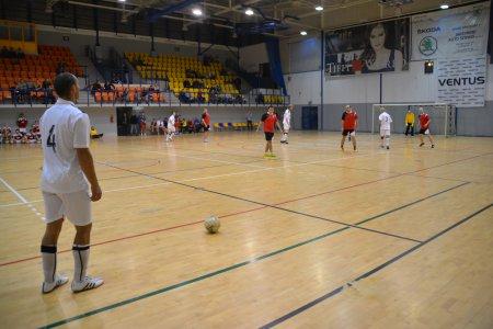 Mecz piłki nożnej rozgrywany w hali sportowo-widowiskowej. Na trybunach grupka widzów