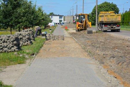 Pośrodku zdjęcia długi chodnik, którego fragment  jest właśnie układany. Po lewej ułożone na trawniku duże kupki brukowej kostki. Po prawej, na jezdni stoi koparka i wywrotka. Szeroki pas między chodnikiem a jezdnią jest pozbawiony trawy i wyrównany pod budowę parkingu