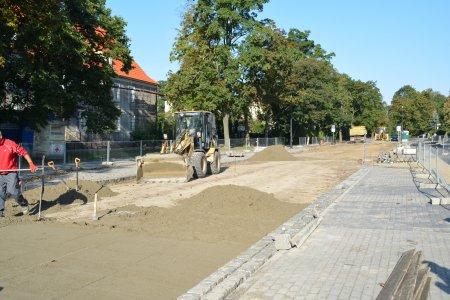 Fragment ul. Sienkiewicza. Po lewej nowy chodnik z kostki, po prawej trwa przygotowywanie podbudowy pod jezdnię. Na placu budowy stoi koparko-ładowarka