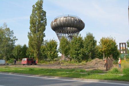 Zdjęcie wieży ciśnień, widok od strony ul. Płockiej. Na placu między ulica i wieżą rozpoczęło się równanie gruntu i montaż ogrodzenia placu budowy