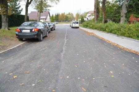 Ulica Bema z nową, równą nawierzchnią. Po lewej stronie, częściowo na jezdni, częściowo na trawniku parkuje kilka samochodów. W oddali widać kilka aut zaparkowanych po prawe stronie wzdłuż chodnika