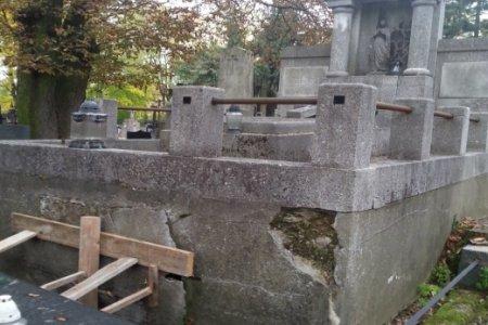 Zabytkowy nagrobek na cmentarzu. Jest zniszczony przez czas. Ma wiele ubytków. Ze strony frontowej zabezpieczony deskami przed rozpadem