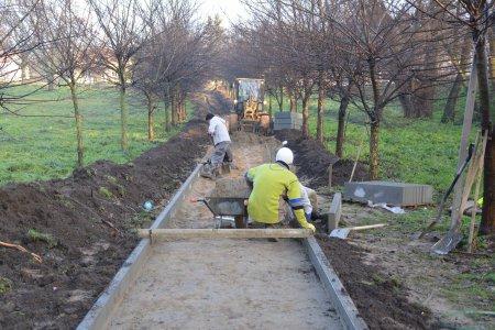 Dwaj pracownicy przygotowują pas gruntu pod położenie torów. Po obu stronach długiego pasa ziemi, z którego zdjęto warstwę trawy, ułożone zostały wąskie, betonowe krawężniki. Po bokach leży nadmiar ziemi, reszta krawężników, narzędzia do pracy. W oddali widać ciągnik.