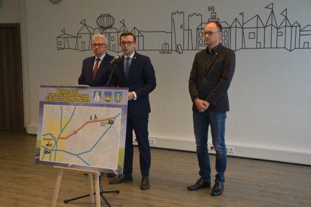 Konferencja prasowa. Przedstawiciele trzech samorządów prezentują tablicę z zaznaczonym przebiegiem planowanej drogi