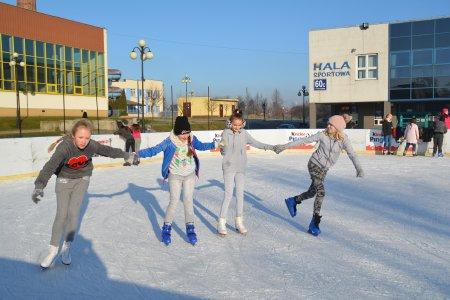 Czwórka dzieci trzymając się za ręce ślizga się po tafli miejskiego lodowiska. Lodowisko co roku rozstawiane jest i zamrażane przed halą sportową przy ul. 17 Stycznia