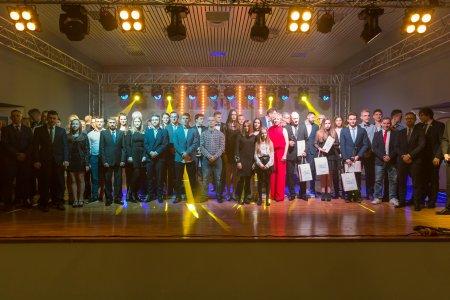 Wspólne, pamiątkowe zdjęcie uczestników gali, którzy stoją na scenie w jednym rzędzie