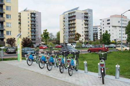 Stacja z miejskimi rowerami na osiedlu mieszkaniowym z wielorodzinnymi blokami