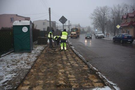 Po lewej trzech robotników w odblaskowych kamizelkach, wymaganych podczas prac na drodze, zdejmują stare, betonowe płyty z chodnika. Po prawej jezdnia i jeżdżące nią samochody