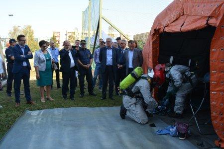 Ratownicy zorganizowali zastępcze miejsce szpitalne. Obserwują to władze miasta, miejscy strażnicy i grupa innych osób