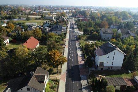 Ulica Kwiatowa z wysoka. Przecina kadr zdjęcia na pół. Widać linie namalowane na jezdni. Op obu stronach ulicy domy i dużo zieleni