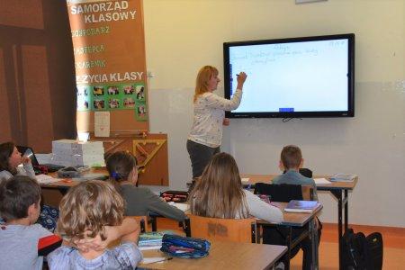 Klasa szkolna. Nauczycielka pisze na interaktywnej tablicy. W ławkach siedzą uczniowie