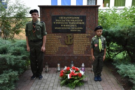 Warta przy pomniku poświęconym ciechanowianom walczącym i poległym w powstaniu warszawskim. Wartę pełnią harcerze: młody mężczyzna i mały chłopiec