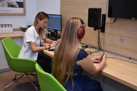 Trwa badanie słuchu. Przy pulpicie siedzą: osoba badająca i badana. Badana ma słuchawki na uszach.