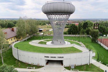 Park Nauki Torus i wieża ciśnień z góry. Dach parku nauki pokryty trawą. Po prawej stronie boisko na terenie należącym do Straży Pożarnej, po lewej budynek