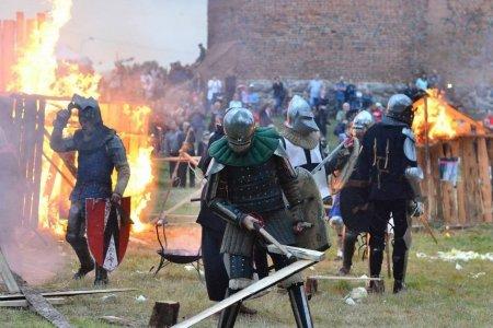 Zamkowe błonia. Trwa historyczna inscenizacja. Rycerze z tarczą i mieczem. Za i9ch plecami płonące drewniane budowle. Dalej publiczność oglądająca wydarzenie