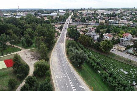 Zdjęcie wykonane z góry. Ulica Płocka z wiaduktem. Po lewej stronie park Marii Konopnickiej a w nim rabata kwiatowa w kształcie terytorium Polski, w barwach flagi narodowej. Po prawej stronie ulicy Płockiej widać zielony labirynt