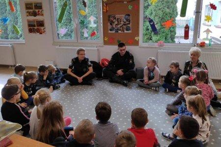 Trwa spotkanie z dziećmi. Dzieci, opiekunka oraz strażniczka miejska i policjant siedzą w kółku na podłodze. Strażniczka mówi. Okna klasy są udekorowane wyciętymi z papieru liśćmi
