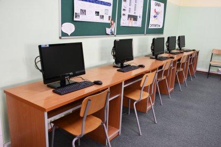 Pod ścianą ustawiony rząd stołów z krzesłami. Na stołach stoi 5 monitorów z klawiaturami i myszkami. Na ścianie przy której stoją stanowiska komputerowe wiszą 3 tablice z informacjami o tematyce informatycznej