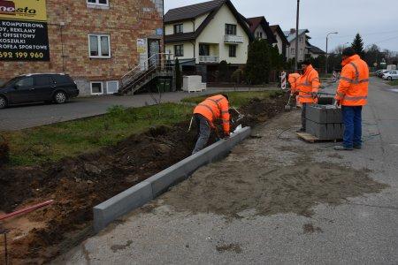 Kilku pracowników w odblaskowych kamizelkach układa krawężnik wzdłuż betonowej nawierzchni. Z połowy trawnika po lewej zebrano warstwę ziemi. W głębi kadru widać zabudowania