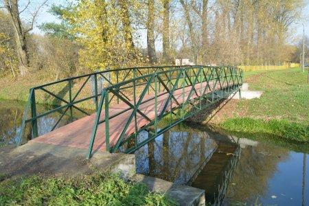 Kładka nad rzeką. Mogą z niej korzystać piesi i rowerzyści. Na metalowej konstrukcji opartej na betonowych blokach ułożono drewniane podłoże. Balustrady z metalowych krzyżujących się długich, wąskich elementów