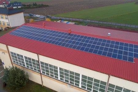 Zdjęcie wykonane z góry. Na dużym, podłużnym szkolnym dachu zamontowano panele fotowoltaiczne