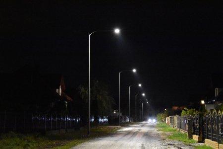 Rząd świecących lamp ulicznych wzdłuż drogi. Po prawej widać ogrodzenia posesji