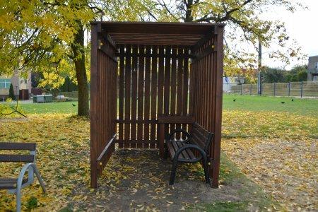 Drewniana, zadaszona konstrukcja zasłonięta pionowymi listwami z trzech stron, wewnątrz której stoi ławka i stolik służący jako miejsce do przewinięcia dziecka