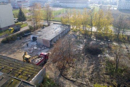Zdjęcie wykonane z wysoka. Teren zaniedbany, nierówna zabłocona nawierzchnia. Po lewej budynek w trakcie rozbiórki. Obok betonowy gruz. Niedaleko budynku stoi koparka i samochód ciężarowy