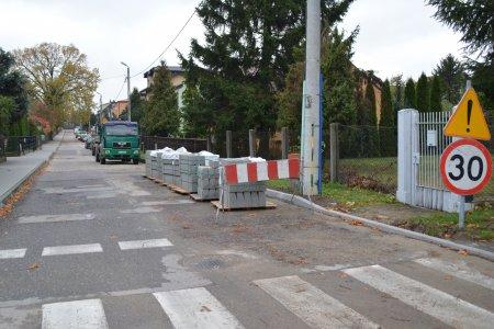 Ulica Borodzicza. Po obu stronach posesje. Tuż za przejściem dla pieszych stoi znak ograniczenia prędkości do 30 km/h. Po prawej stronie ulicy ustawiono rząd palet z krawężnikami, dalej stoi ciężarówka, a za nią zaparkowane auta.