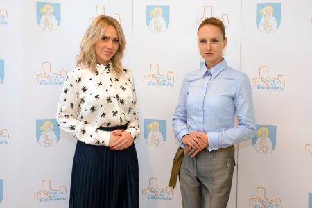 Dwie kobiety stoją na tle ścianki z logo miasta. Z lewej dotychczasowa rzecznik Urzędu Miasta Renata Jeziółkowska, po prawej nowa rzecznik Paulina Rybczyńska