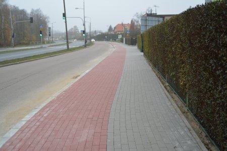 W kadrze długi chodniki i ścieżka dla rowerów wybudowane wzdłuż jezdni