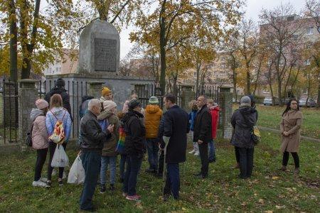 Grupa ludzi przed lapidarium upamiętniającym pomordowanych Żydów. Większość zgromadzonych to młodzież w wieku szkolnym.