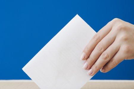 Kobieca dłoń trzymająca kartkę w sposób przywodzący na myśl kartę do głosowania wkładaną do urny wyborczej