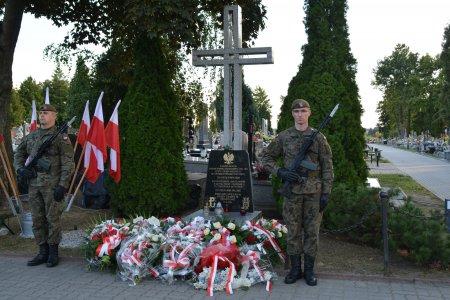 Na miejskim cmentarzu po obu stronach krzyża o wysokości około 3m stoją dwaj żołnierze. W dolnej części krzyża tablica z orłem na górze i napisami poniżej. Przed krzyżem leżą wiązanki kwiatów. Za plecami żołnierza po lewej widać stojak, w którym ustawiono narodowe flagi.