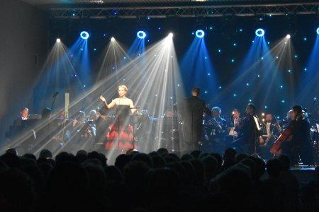 Na scenie trwa koncert. Śpiewa kobieta w sukni z odkrytymi ramionami. Za nią widać orkiestrę. Z góry scenę oświetlają reflektory, które tworzą piękne smugi świateł