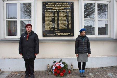 Tablica na ratuszu, na której zapisano nazwiska osób zamordowanych przez hitlerowców tuż przed 17 stycznia. Po obu stronach tablicy stoi watra. Pod tablicą złożono kwiaty