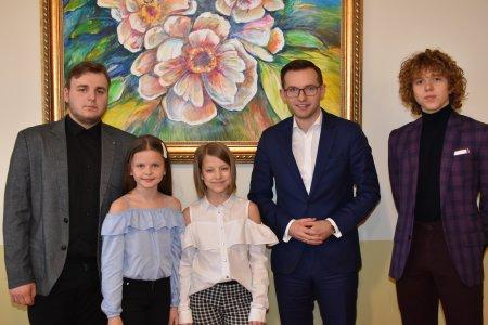 Stypendyści prezydenta Ciechanowa na pamiątkowym zdjęciu z prezydentem Krzysztofem Kosińskim. Wszyscy stoją na tle ściany z wielkim obrazem z różowymi kwiatami