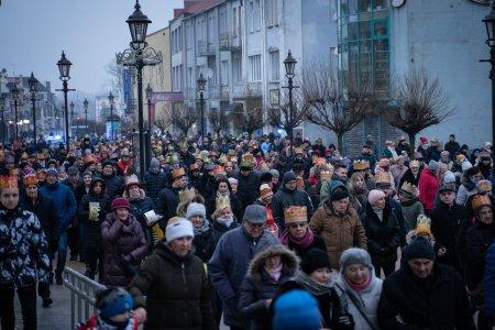 Ulica Warszawska na całej szerokości wypełniona ludźmi uczestniczącymi w Orszaku Trzech Króli. Jest szaro, niebo zachmurzone