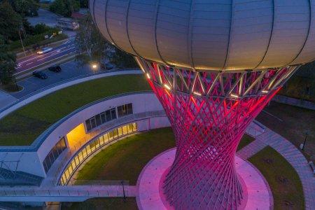 Zdjęcie wykonane o zmierzchu przy pomocy drona latającego na wysokości okrągłego zbiornika wieży. Wieża pięknie oświetlona od dołu na ciemny róż, amarant. Z okien parku nauki u stóp wieży pada żółte światło.