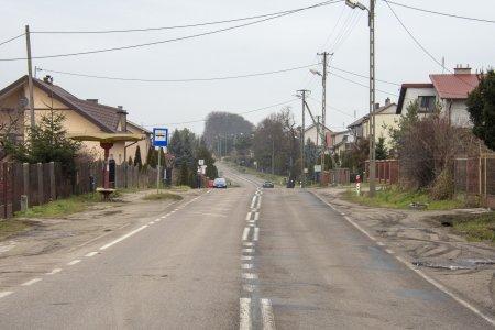 Ulica ze zniszczoną nawierzchnią. Podzielona liniami na dwa pasy przeciwnych kierunków ruchu. Widoczne linie brzegowe jezdni. Po obu stronach nierówne, gruntowe pobocze. Brak chodników. Po lewej stronie widać zadaszony przystanek autobusowy i niedużym siedzeniem dla pasażerów. Po obu stronach ulicy domy jednorodzinne
