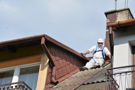 Dwa sąsiadujące dachy, Jeden z nich jest pokryty płytami falistymi z azbestu. Na tym dachu siedzi mężczyzna ubrany w biały kombinezon ochronny