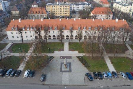 Krzywa hala po gruntownym remoncie. Zdjęcie zrobione z wysoka. Dzięki temu w kadrze mieści się cały długi budynek, wybudowany na planie łagodnego łuku. Na dachu ma pomarańczową dachówkę, ściany białe. Przed halą jest park z alejkami i monument poświęcony Marszałkowi Józefowi Piłsudskiemu. Za halą są bloki mieszkalne.